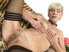Пожилая блондинка в чулках ласкает свою бритую пизду