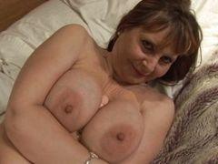 Зрелая с большой грудью трахает себя с дилдо