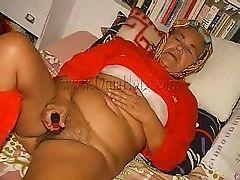 Возбужденная бабуля лежит на кровати и мастурбирует